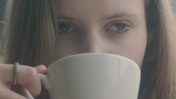 Hand-held shot of a woman drinking from a mug Royalty-free stock video