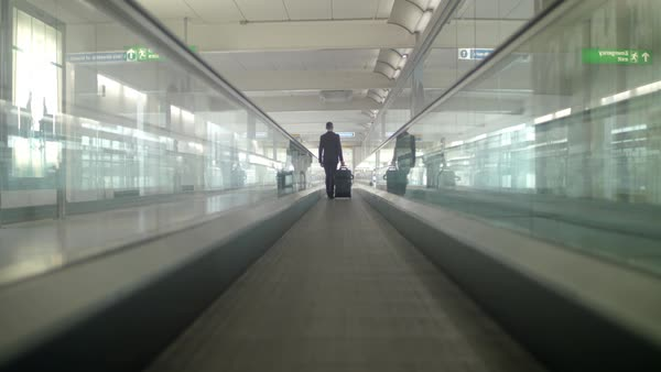 Tracking shot of a man pulling his suitcase on a moving walkway Royalty-free stock video