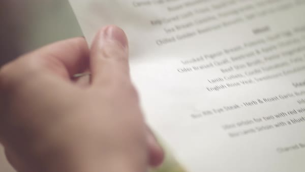 Hand-held shot of a person reading a menu in a restaurant Royalty-free stock video