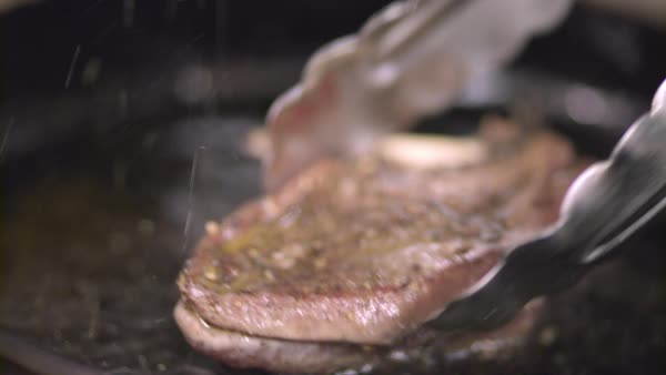 Hand-held shot of a person turning over a frying duck breast with kitchen tongs Royalty-free stock video