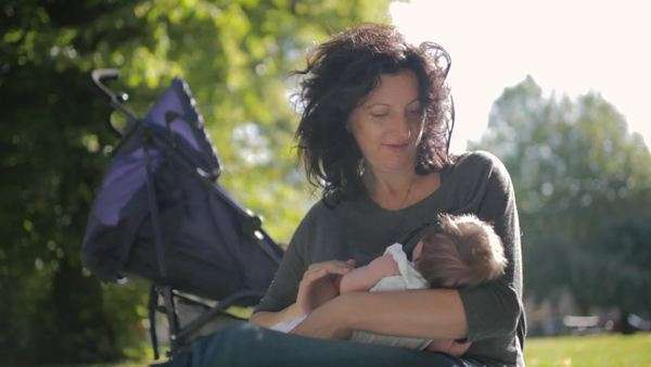 Medium shot of a woman breast feeding her child in a park Royalty-free stock video