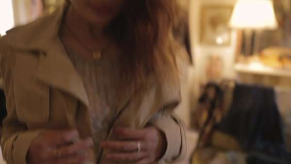 Medium close-up shot of a woman trying on a coat in a boutique Royalty-free stock video