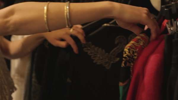 Medium close-up shot of a woman browsing clothes in a boutique Royalty-free stock video