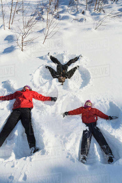 A family making snow angels in wintertime; Talkeetna, Alaska, United States of America Royalty-free stock photo