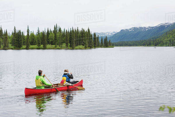 Family in red canoe on Byers Lake with green tree covered shoreline and mountain foothills in the background, Denali State Park; Alaska, Alaska, United States of America Royalty-free stock photo