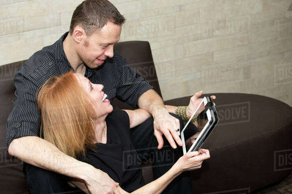 A couple looking at a tablet together, wife with a disability; Edmonton, Alberta, Canada Royalty-free stock photo