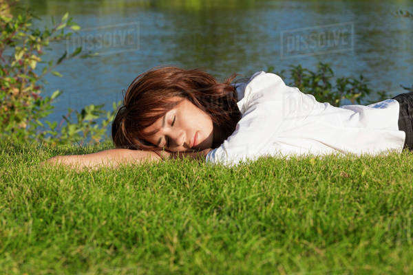 Young woman laying down and relaxing in a park; Edmonton, Alberta, Canada Royalty-free stock photo