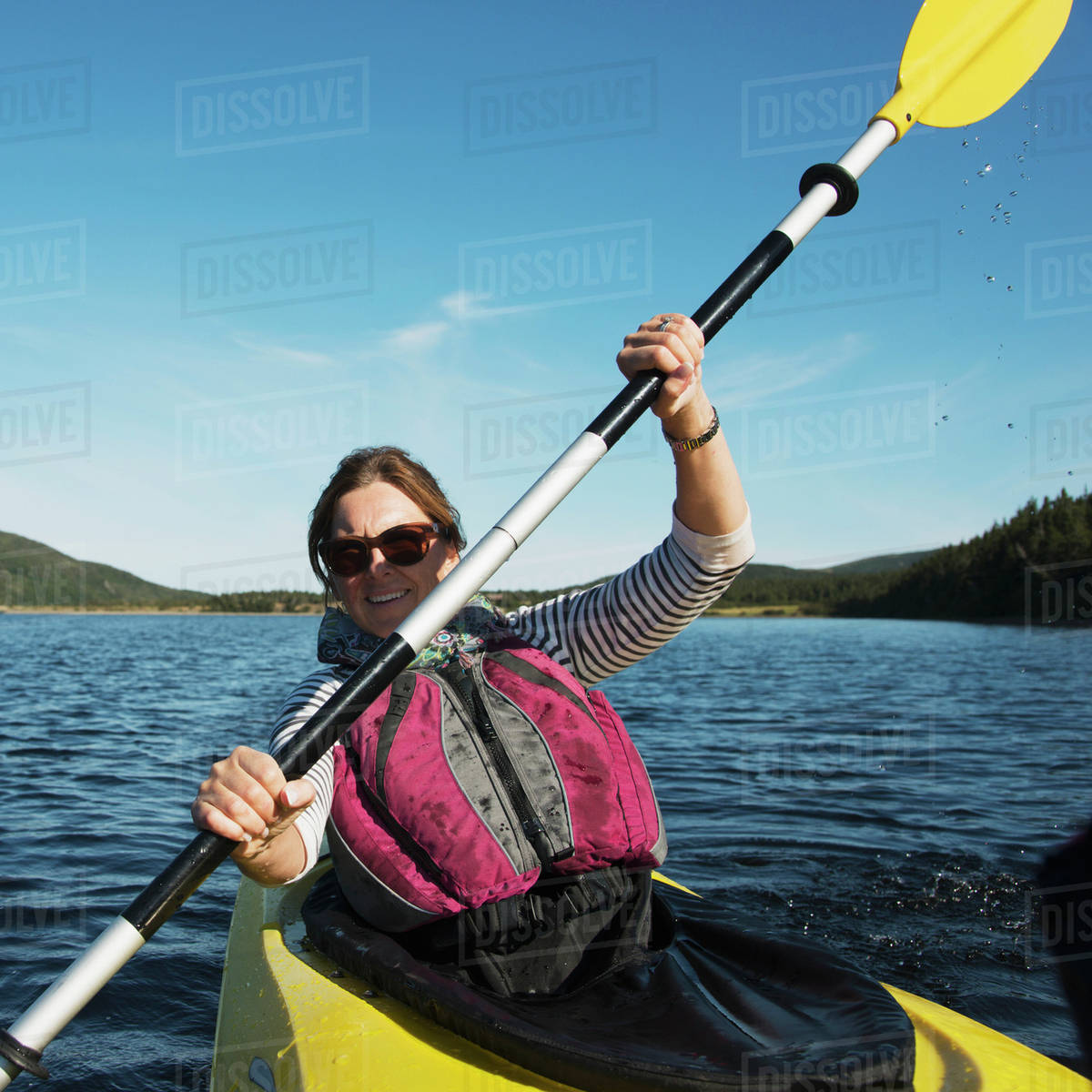 a woman with a paddle in a kayak in gros morne national park trout