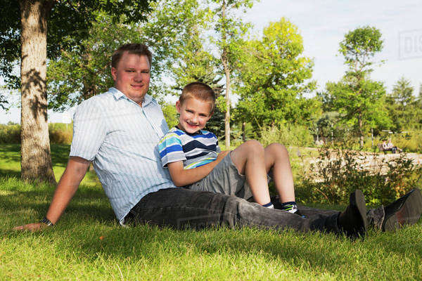 Portrait of a father and son hanging out in a park; Edmonton, Alberta, Canada Royalty-free stock photo