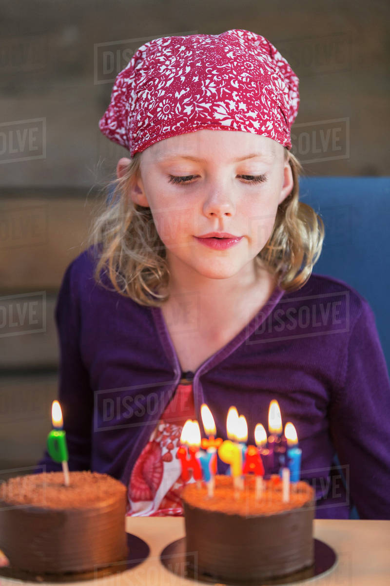 Young Girl Wearing Red Bandana On Her Head And Blowing Out The Candles Of A Birthday Cake Anchorage Alaska United States Of America Stock Photo
