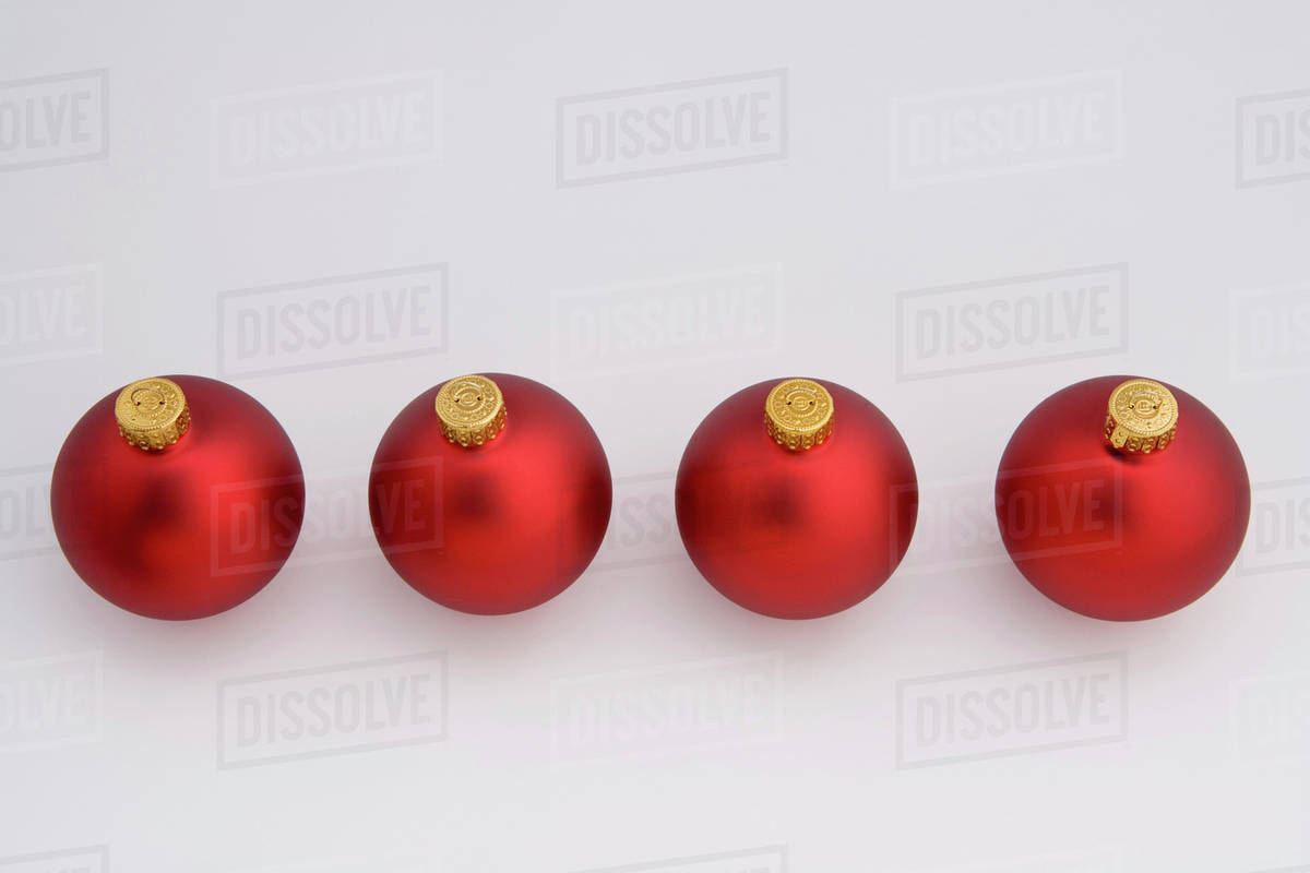 four red christmas balls in a diagonal line on white background studio portrait - Red Christmas Balls