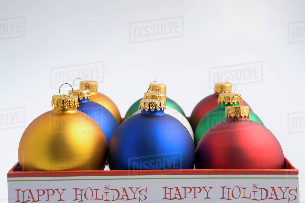 desaturated christmas tree bulb ornaments in happy holidays box studio portrait