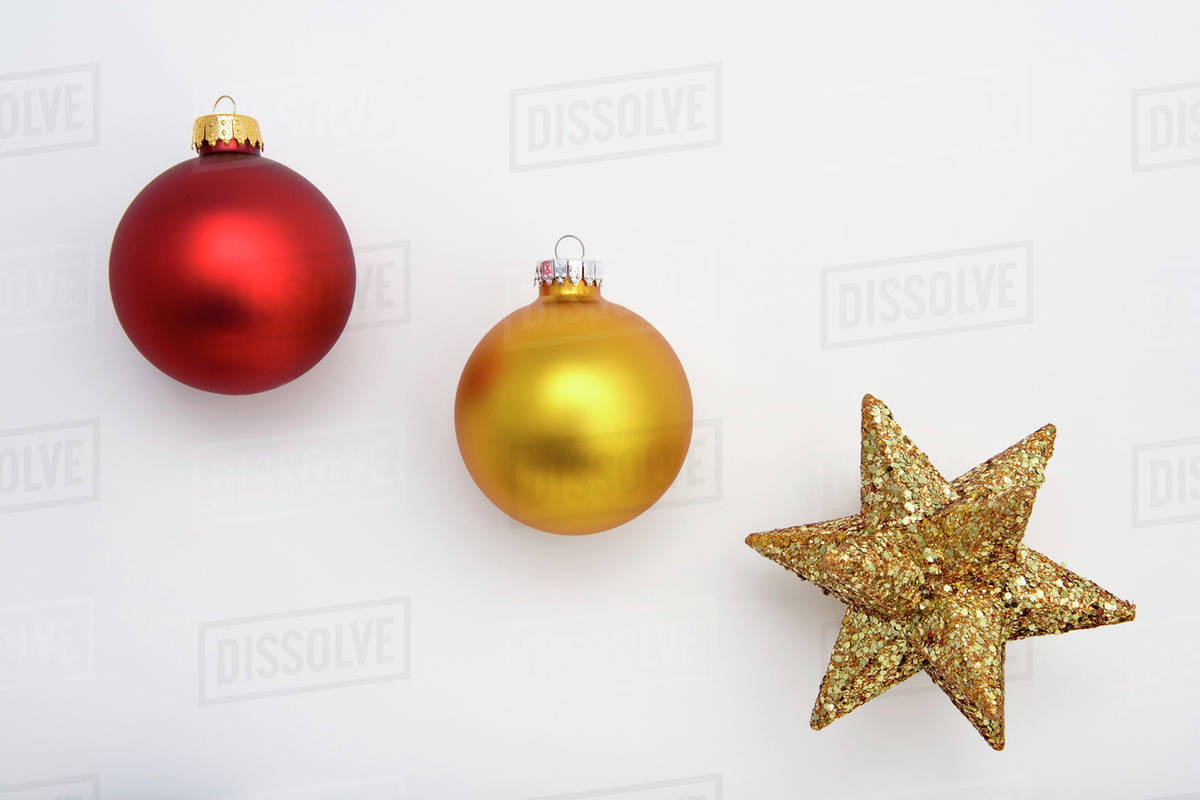 two christmas tree bulb ornaments in row with star ornament on white background studio portrait