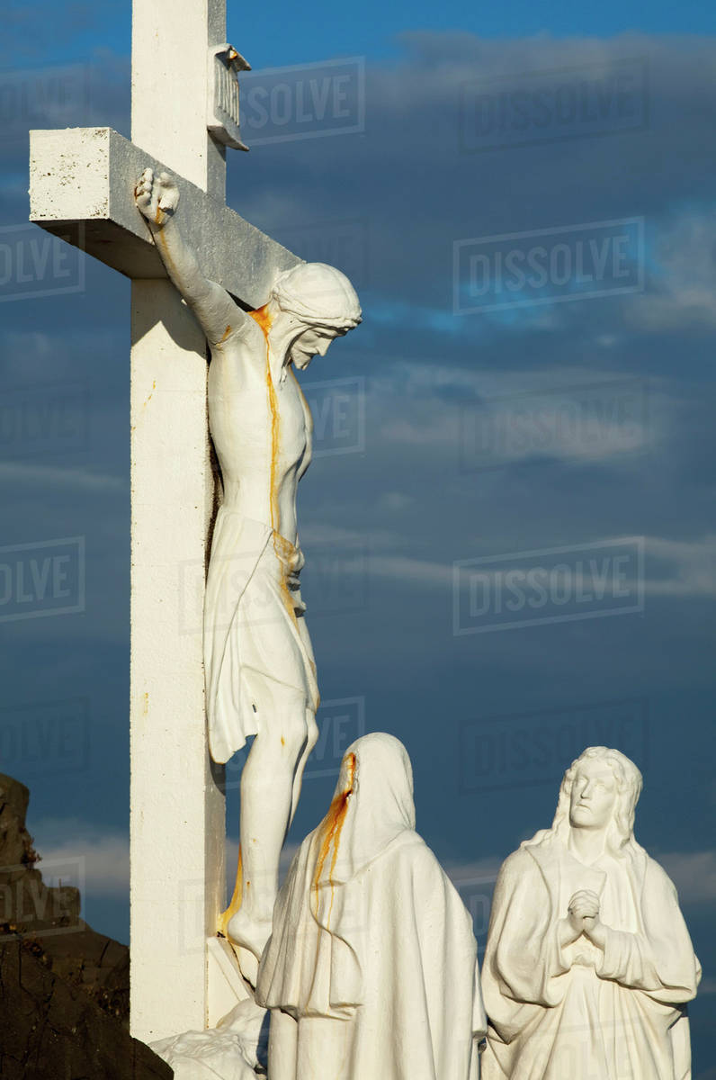 Statue of jesus christ on the cross with two women at the foot of the  cross