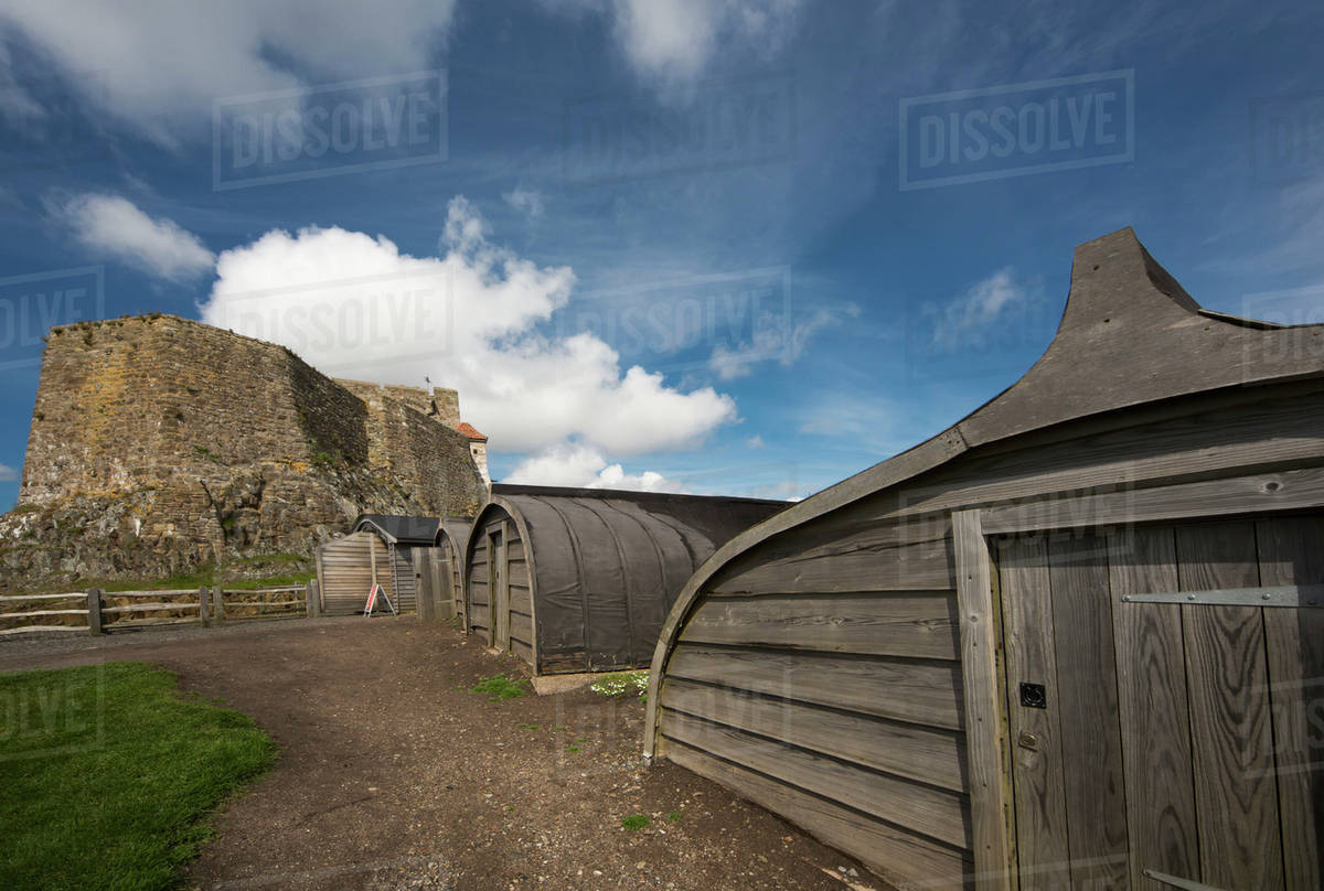 rounded wooden buildings and a stone building on holy island