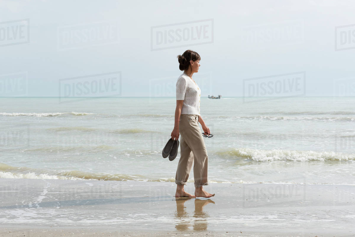 A Woman Walking On The Wet Beach Carrying Her Shoes D869 28 015