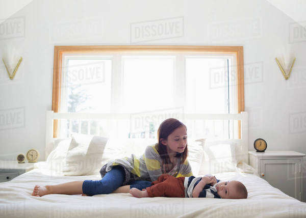 A sister playing with her baby brother on a bed at home; Victoria, British Columbia, Canada Royalty-free stock photo