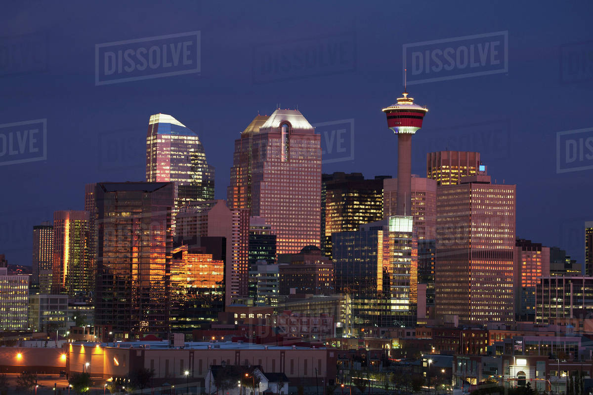 calgary skyline at dawn with city lights and deep blue sky with