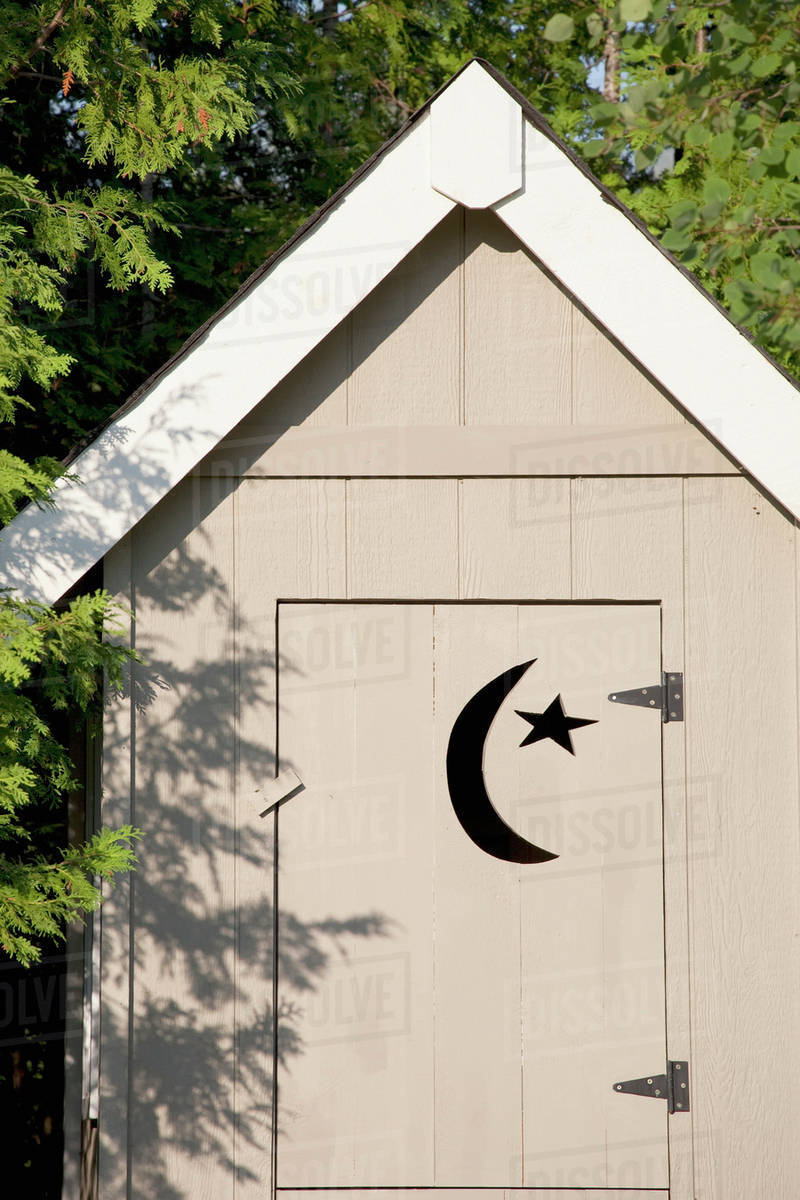 Close Up Of Wooden Outhouse With Crescent Moon And Star Cut Out On