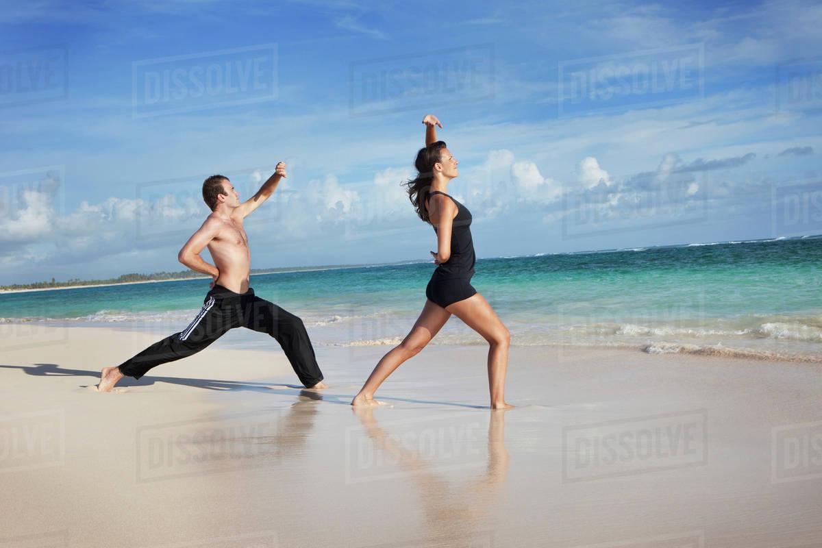 A Man And Woman Doing Yoga On The Beach Punta Cana La Altagracia Dominican Republic