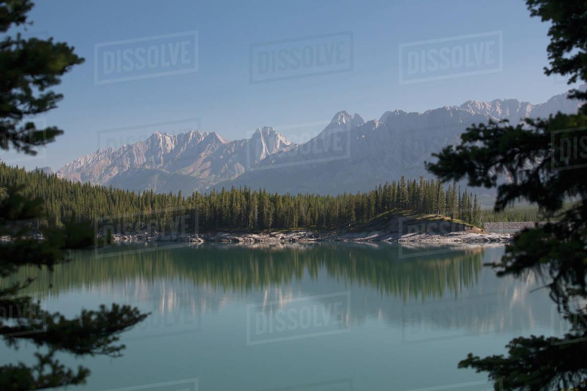 Mountain lake reflecting mountain range at sunrise framed by ...