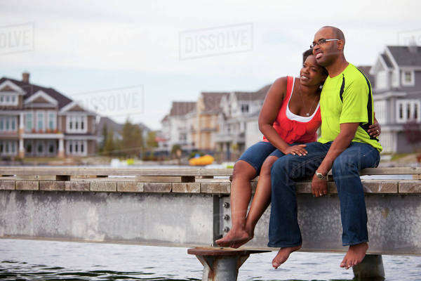 Husband And Wife Spending Time Together On A Pier In A Residential Setting; Edmonton, Alberta, Canada Royalty-free stock photo