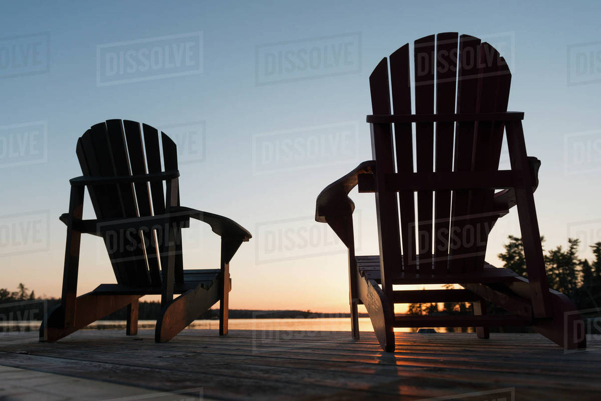 Silhouette Of Adirondack Chairs On A Wooden Dock Along A Lake At Sunset;  Ontario, Canada
