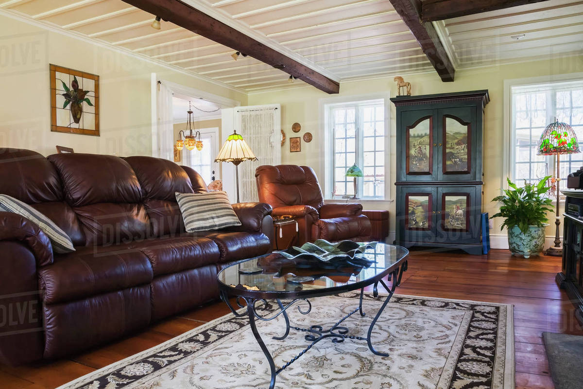 Brown Leather Sofa Chair And Wooden Armoire In The Living Room Inside An Old Reconstructed 1886 Canadiana Cottage Style Residential Home Quebec Canada