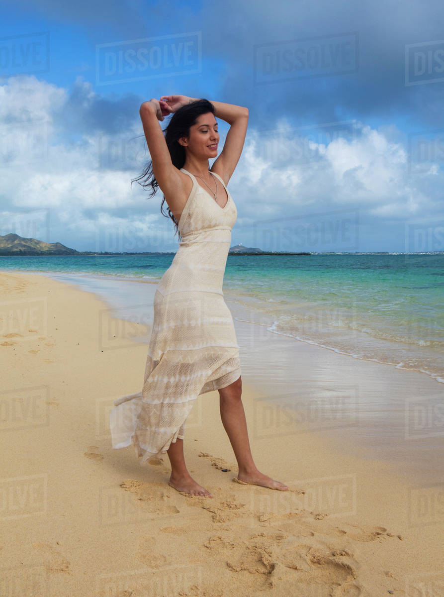Young woman in white dress on the beach at the water's edge; Kailua, Island  of Hawaii, Hawaii, United States of America - Stock Photo - Dissolve