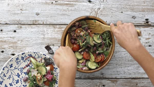 Woman's hands tossing, and dishing salad, ready to eat. Royalty-free stock video