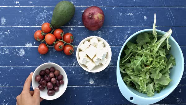 Woman's hands setting out ingredients for Greek salad recipe. Royalty-free stock video