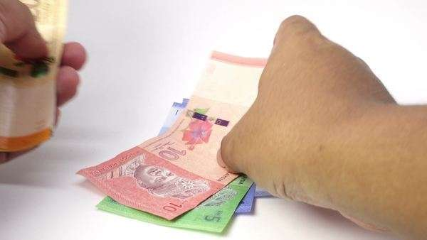 Malaysia Ringgit coins falls on banknotes on black background