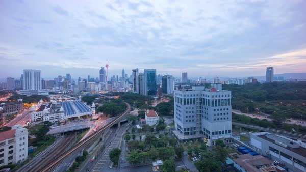 Timelapse of a beautiful sunrise of Kuala Lumpur city view from rooftop of a building with moving vehicle, clouds and sunlight burst. Zoom in Royalty-free stock video
