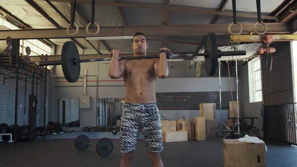 Man does weight lifting as part of his workout routine in gym Royalty-free stock video
