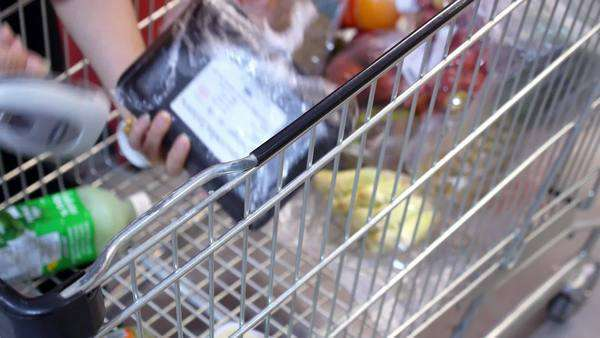 Cashier at cash desk and trolley with food products in supermarket. Close-up. Royalty-free stock video