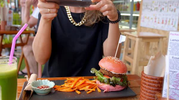 Trendy woman taking photo of vegetarian burger with smartphone in cafe Royalty-free stock video