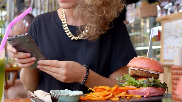 Stylish woman with phone in cafe with healthy veggie burger and carrot french fries Royalty-free stock video