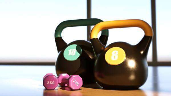 A pair of black kettlebell and pink dumbbell on hardwood floor Royalty-free stock video