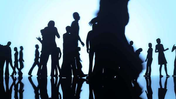 Silhouettes of a crowd of people walking on a reflective surface past a bright background Royalty-free stock video