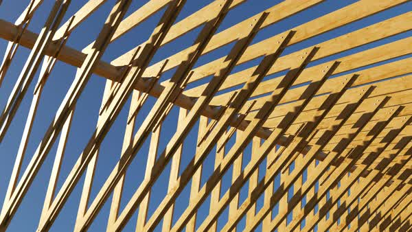 Construction site wooden roof structure of unfinished building. Loopable with sky in the background. Royalty-free stock video