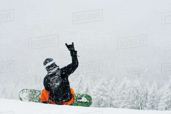 Rear view of a person with snowboard gesturing while sitting on snow Royalty-free stock photo