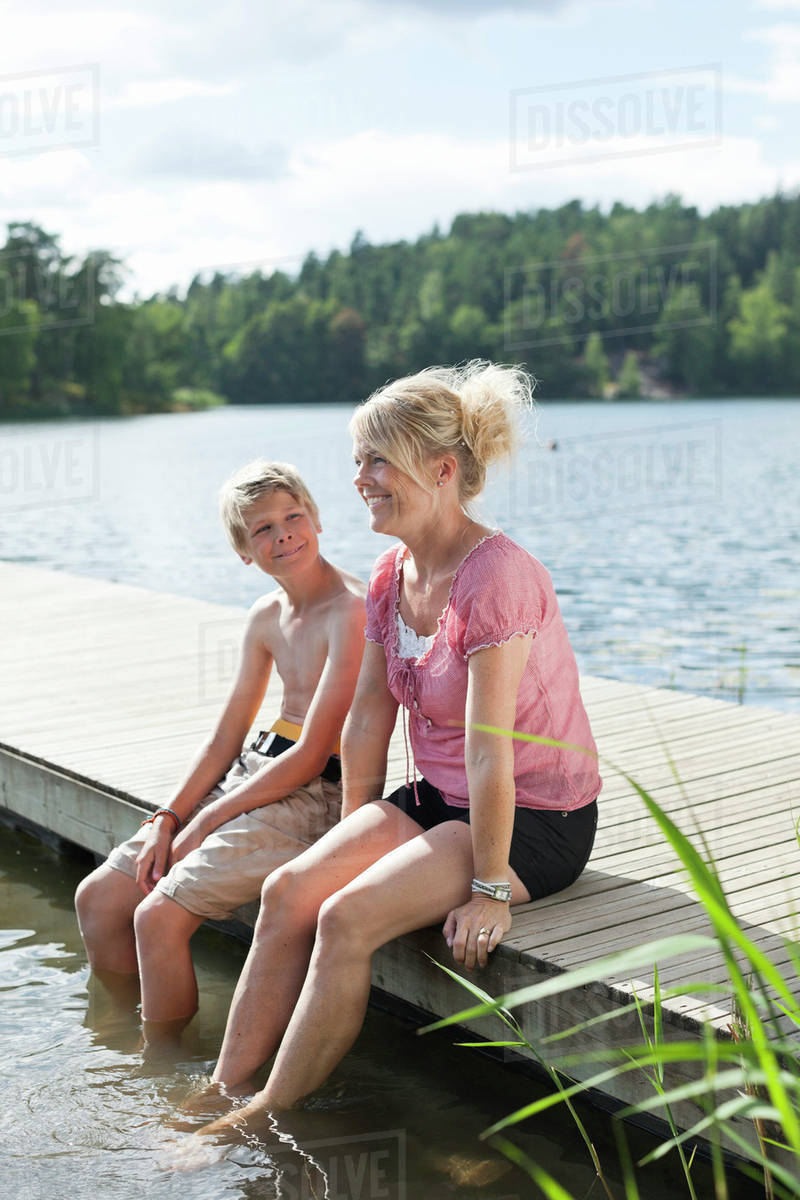 Happy Mature Woman Sitting With Son On Pier During -1240