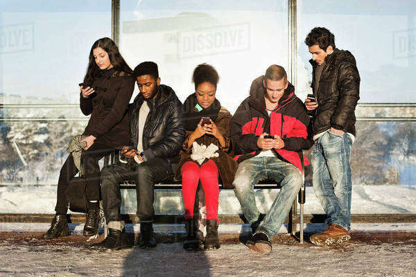 Group of multi ethnic friends using mobile phones on bench Royalty-free stock photo
