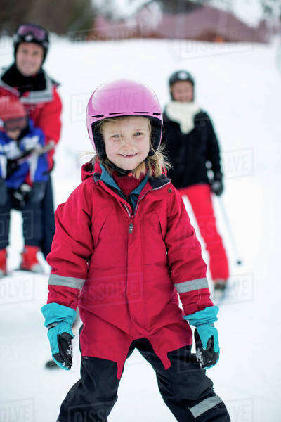Portrait of girl in ski-wear with family in background Royalty-free stock photo
