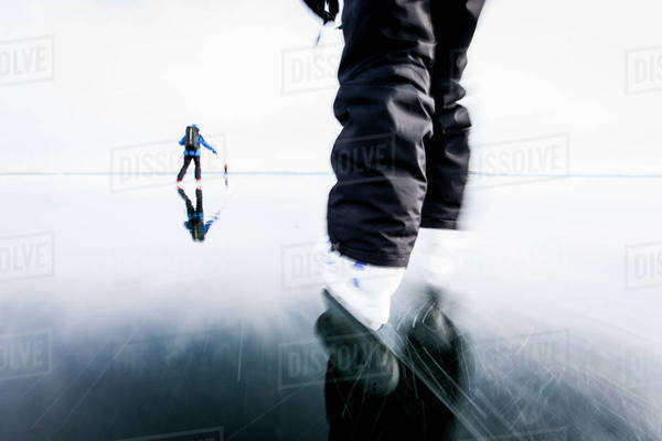 People skiing on frozen lake against clear sky Royalty-free stock photo