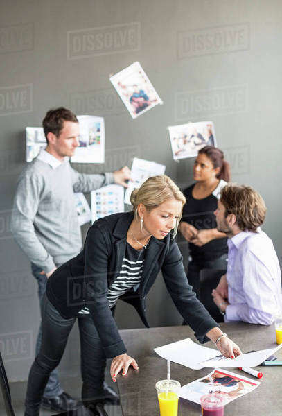 Mid adult businesswoman looking at paper at desk with colleagues discussing in background Royalty-free stock photo