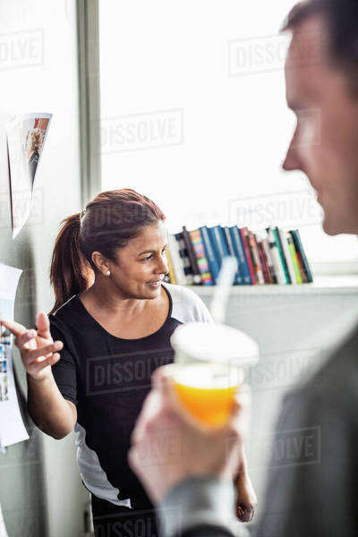 Mature businesswoman giving presentation with male colleague in foreground Royalty-free stock photo