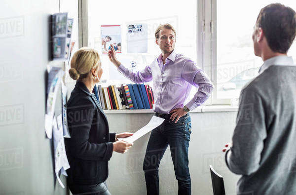 Business colleagues discussing over photograph in office Royalty-free stock photo