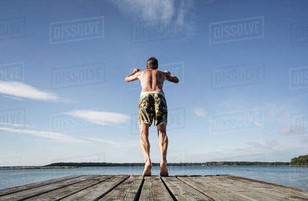 Rear view of mature man diving into sea Royalty-free stock photo