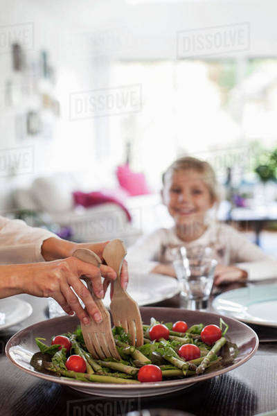 Cropped image of woman serving salad at dining table Royalty-free stock photo